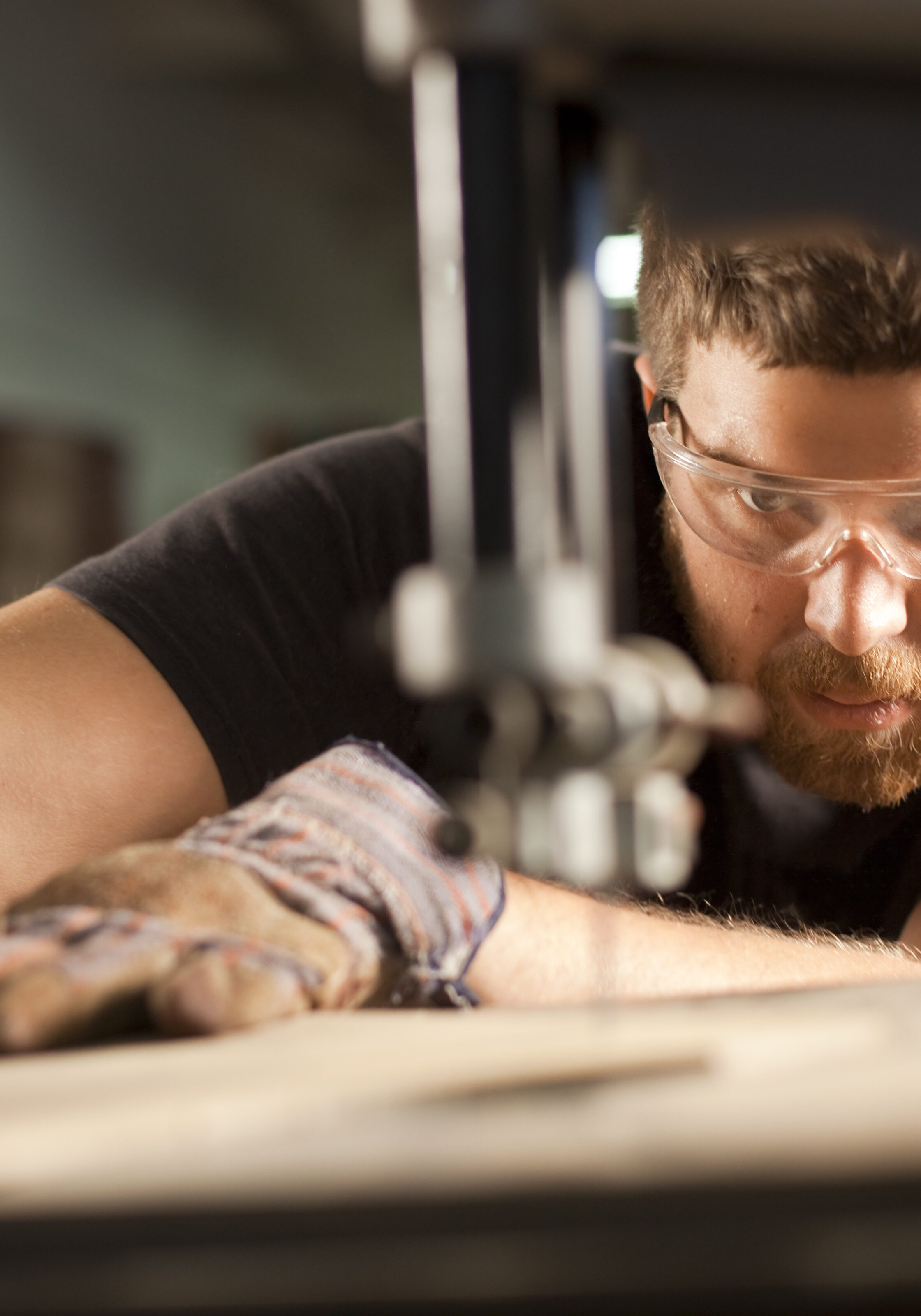 A man using a bandsaw, also known as a jigsaw or a scroll saw, cuts through a piece of wood.  Very shallow depth of field.